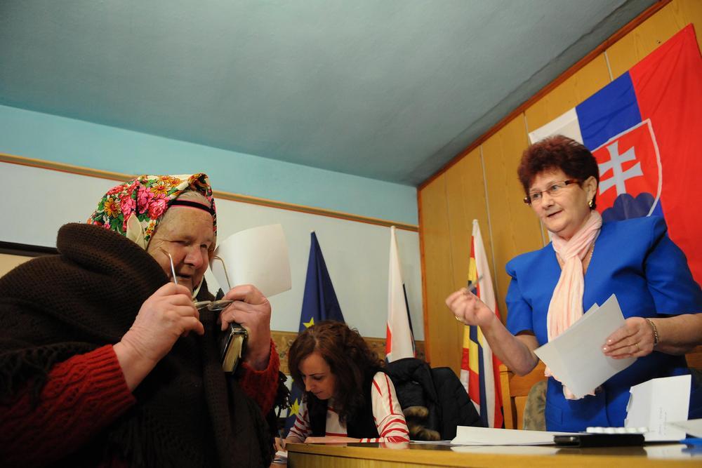 Žena v kroji si preberá hlasovací lístok v obci Lendak v okrese Kežmarok.
