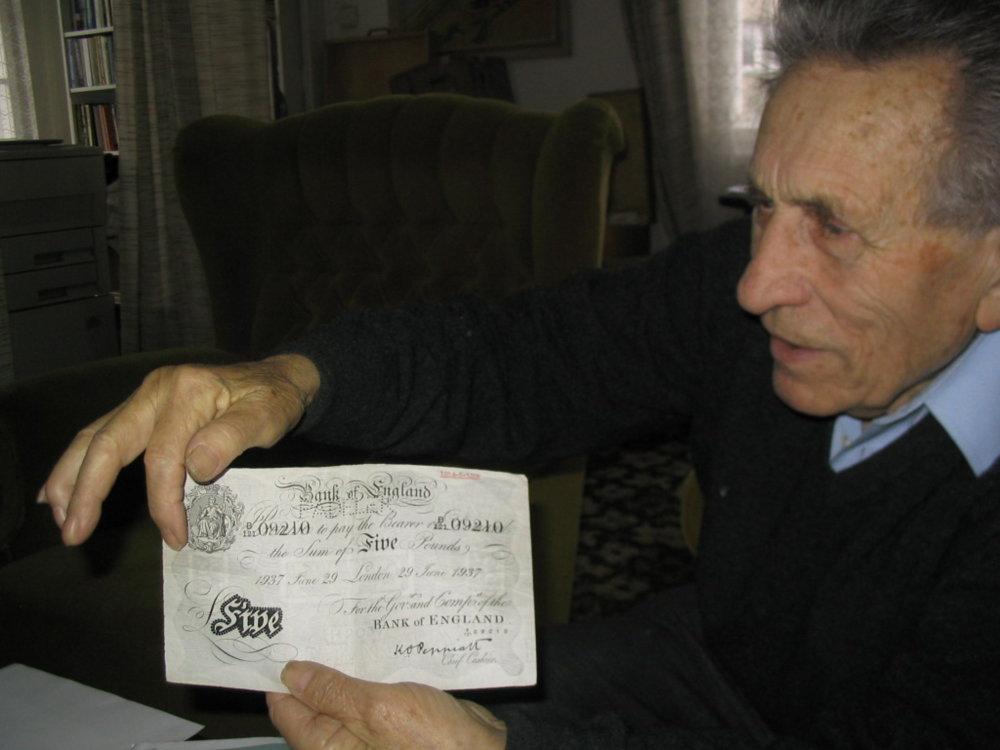 Adolf Burger ukazuje kópiu jednej z falošných bankoviek. Foto - Postbellum