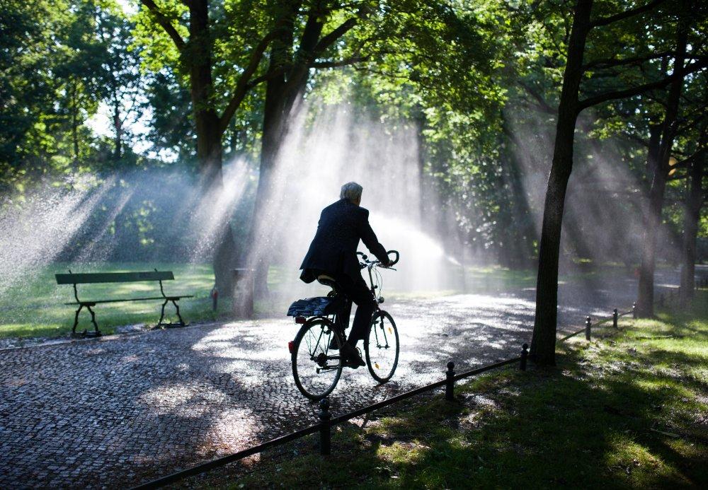 KK27 Berlín - Muž prechádza na bicykli v parku 10. júna 2015 v Berlíne. FOTO TASR/AP A cyclist rides by a lawn sprinkler in the Tiergarten park in Berlin, Wednesday morning, June 10, 2015. (Lukas Schulze/dpa via AP)