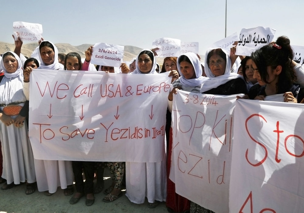 Yazidi Kurdish women hold posters and banners during a protest against the Islamic State group's invasion on Sinjar city one year ago, in Dohuk, northern Iraq, Monday, Aug. 3, 2015. Thousands of Yazidi Kurdish women and girls have been sold into sexual slavery and forced to marry Islamic State militants, according to Human Rights organizations, Yazidi activists and observers. (AP Photo/Seivan M.Salim)