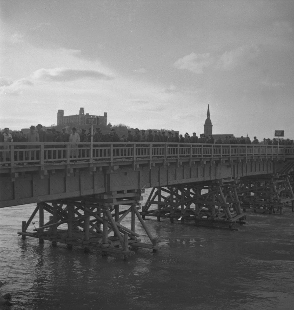 Na archívnej snímke z 28. apríla 1945 v Bratislave slávnostné otvorenie dunajského mosta pred tzv. Múzeom hygieny. FOTO TASR - Jozef Teslík *** Local Caption *** archív archívna snímka fotografia sken scan doèasný drevený most otvorenie rieka Dunaj doprava vojna druhá svetová vojna oslobodenie Bratislavský hrad výstavba stavebníctvo