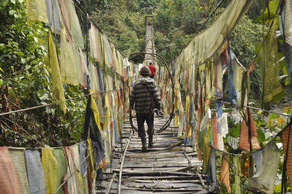 Po moste posiatom modlitebnými vlajkami pred chrámom Dewakota v Indii sa ročne prejde iba pár cudzincov.