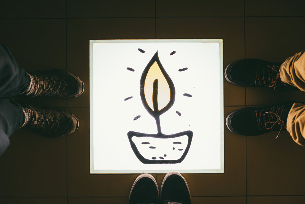 Pri vstupe do poradenského centra v Plamienku je na zemi svetelná tabuľa s ich logom. Foto: Jakub Čaprnka