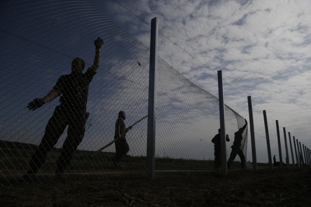 "KK31 Beremend - Maïarskí vojaci stavajú plot na hranici s Chorvátskom neïaleko maïarskej obce Beremend 22. septembra 2015. FOTO TASR/AP Hungarian soldiers work on a fence that is being built at the border with Croatia, near the village of Beremend, Hungary, Tuesday, Sept. 22, 2015. Hungary's prime minister Viktor Orban said that millions of migrants are ""laying siege"" to the borders of his country and of Europe, putting the continent in danger. (AP Photo/Petr David Josek)"