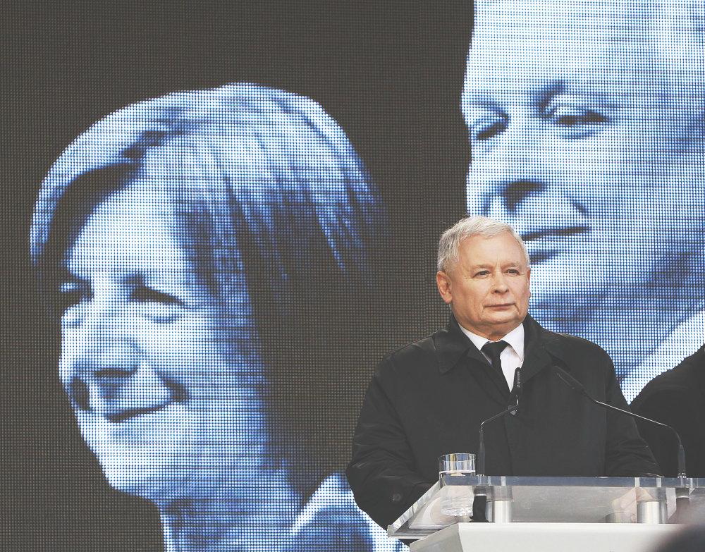 Šéf poľskej vládnej strany Jaroslaw Kaczynski, v pozadí fotografia jeho brata Lecha, ktorý zahynul pri páde lietadla pri ruskom Smolensku v roku 2010. Práve od vládnej strany PiS sa šíria konšpiračné teórie, podľa ktorých bol pád lietadla atentátom. Foto – Tasr