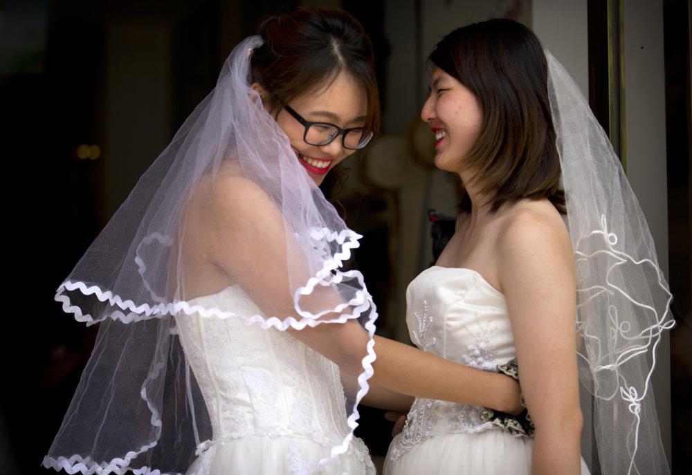 KK31 Peking – Èínsky lesbický pár Li Tching-tching (vpravoa) a Teresa Su sa umievajú poèas príprav na ich svadbu 2. júla 2015 v Pekingu. Prominentný èínsky lesbický pár uzavrel neformálne manželstvo v rámci snáh o uzákonenie zväzkov medzi osobami rovnakého pohlavia v Èíne. Li Tching-tching a Teresa Su si vymenili manželské s¾uby a prstene štyri mesiace po tom, ako prvú z partneriek zadržali èínske orgány v súvislosti s jej aktivizmom za práva žien. Vo väzbe vtedy strávila vyše mesiaca. FOTO TASR/AP Teresa Xu, left, and Li Tingting, right, share a moment outside of a beauty salon where the two were preparing for their wedding in Beijing, Thursday, July 2, 2015. A prominent Chinese lesbian couple held a simple ceremony Thursday to announce their informal marriage, in their latest effort to push for legalization of same-sex unions in China. (AP Photo/Mark Schiefelbein)