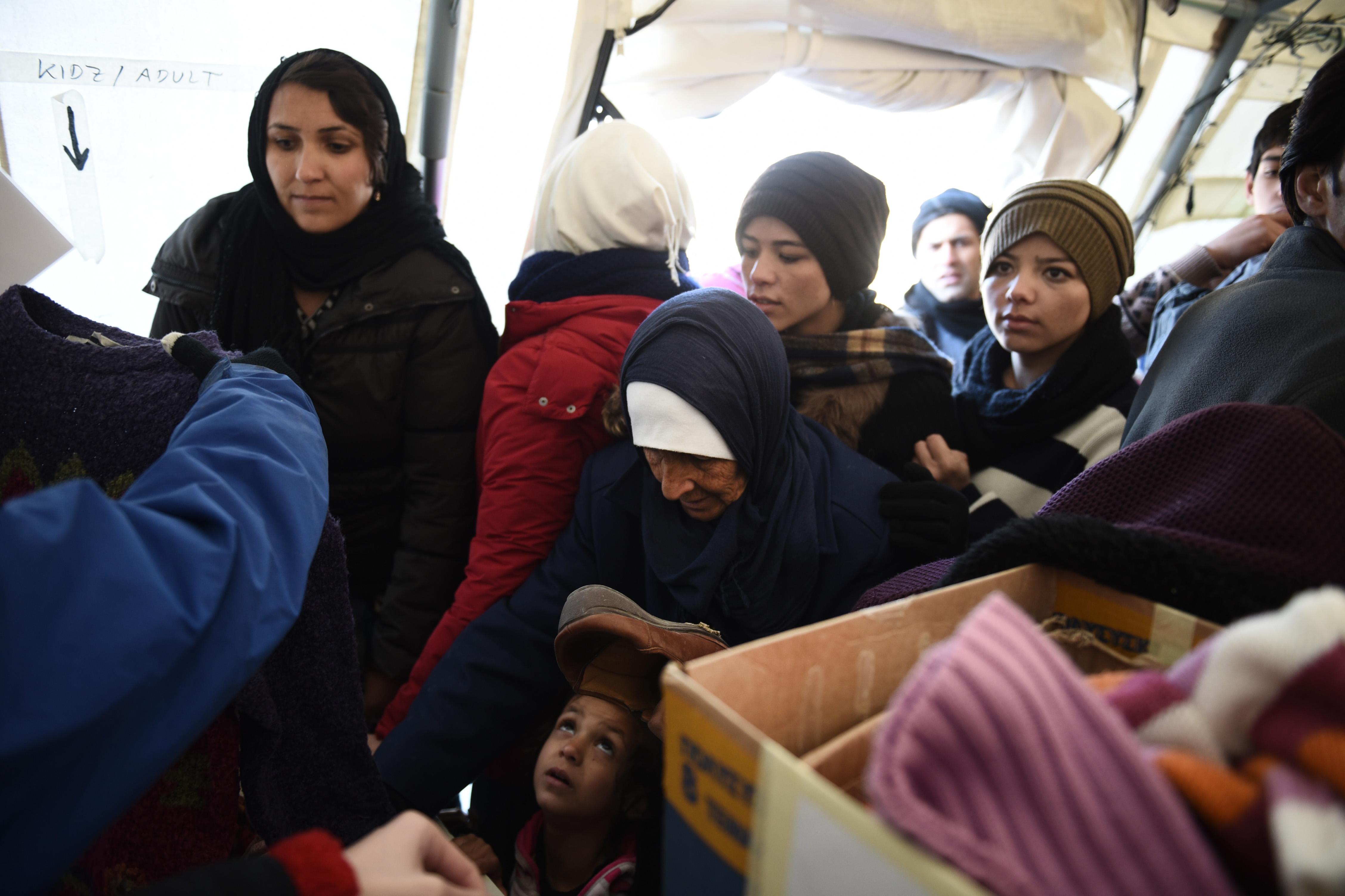 Utečenci čakajú na oblečenie. Foto – TASR/AP
