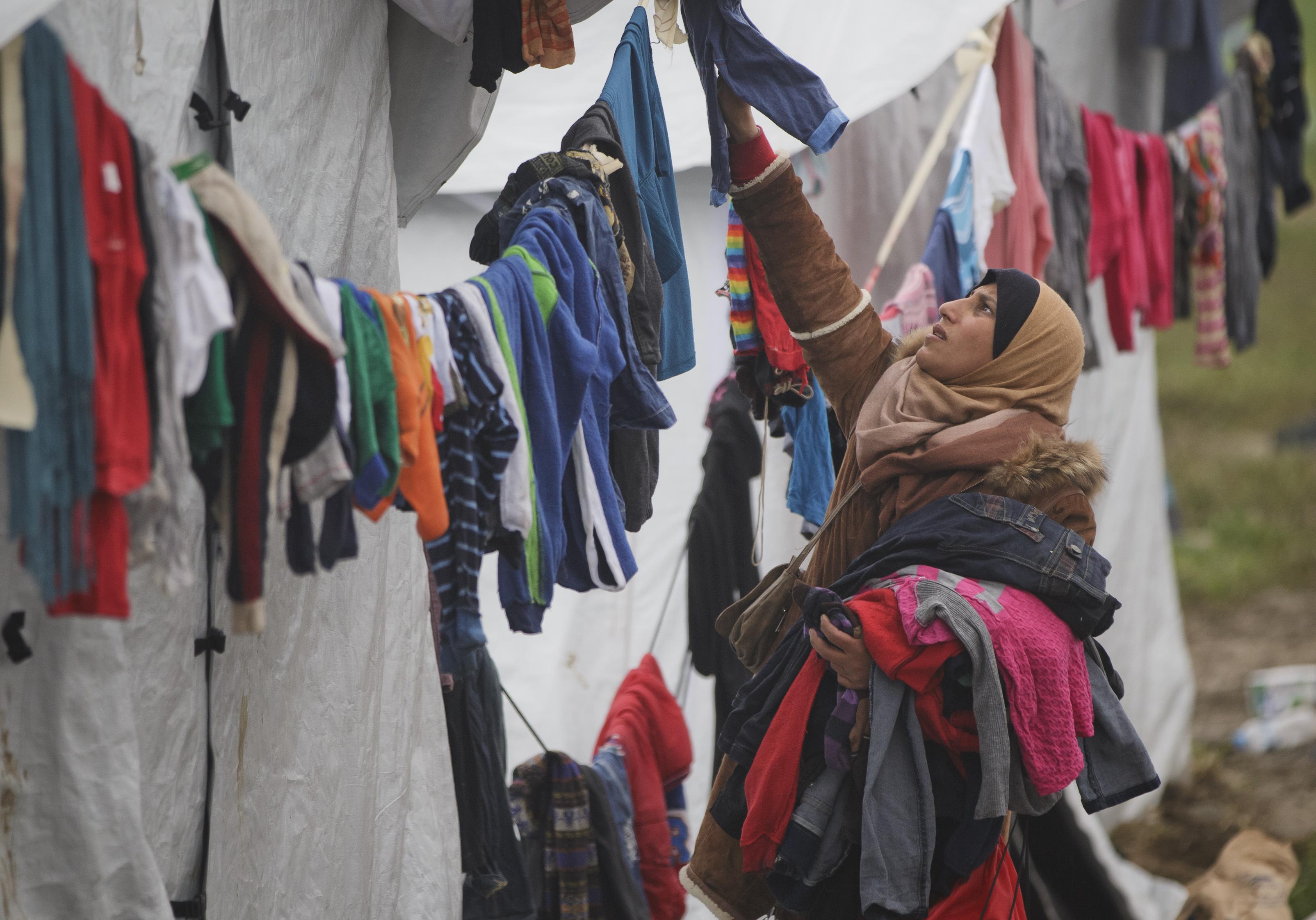 Migrantka veššia oblečenie pri stane v tábore pri Idomeni. Foto - TASR/AP