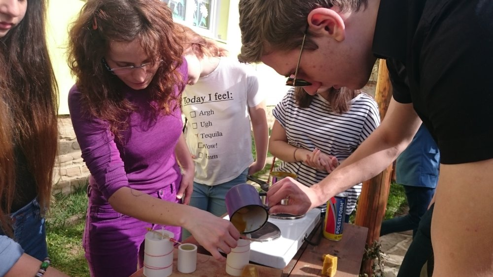 Učiteľka Táňa (vľavo) pomáha študentovi z Litvy pri odlievaní sviece z včelieho vosku. Foto N – Laco Kerekes