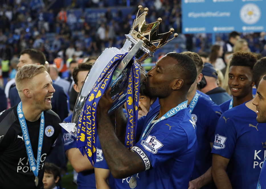 Leicester's Wes Morgan kisses the trophy as Leicester City celebrate becoming the English Premier League soccer champions at King Power stadium in Leicester, England, Saturday, May 7, 2016.(AP Photo/Matt Dunham)