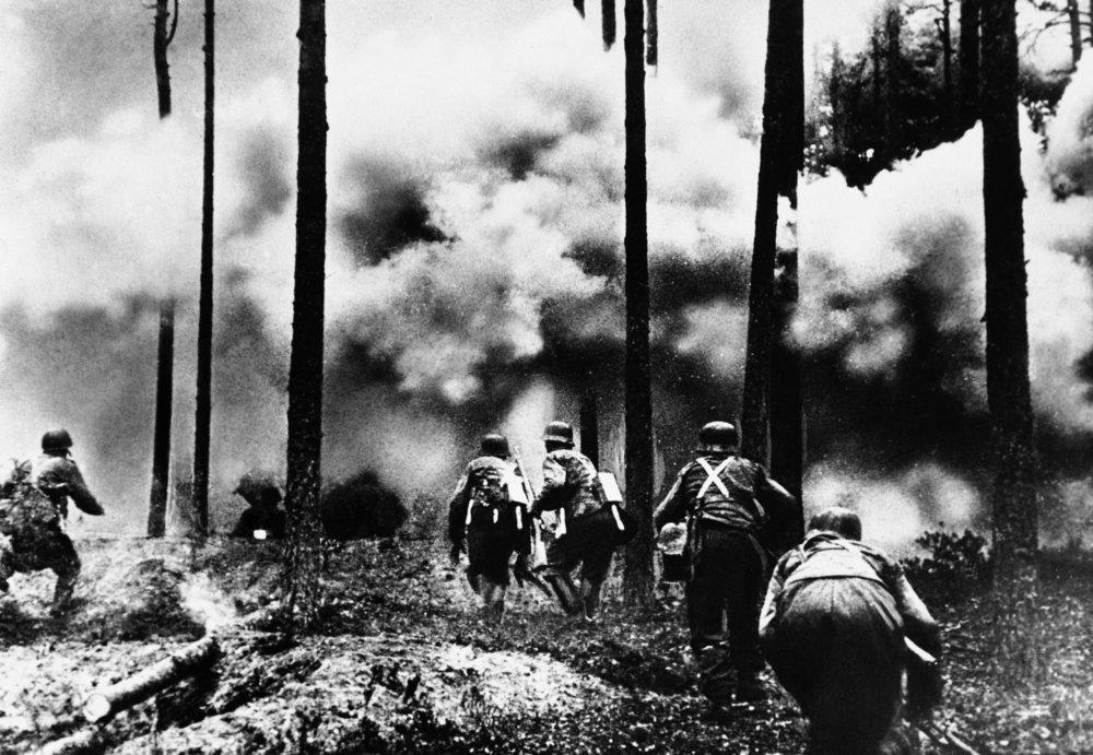 Na archívnej snímke z 26. novembra 1941 vojaci prechádzajú cez horiaci les v severnej časti ruského frontu počas obliehania Leningradu. FOTO - TASR/AP