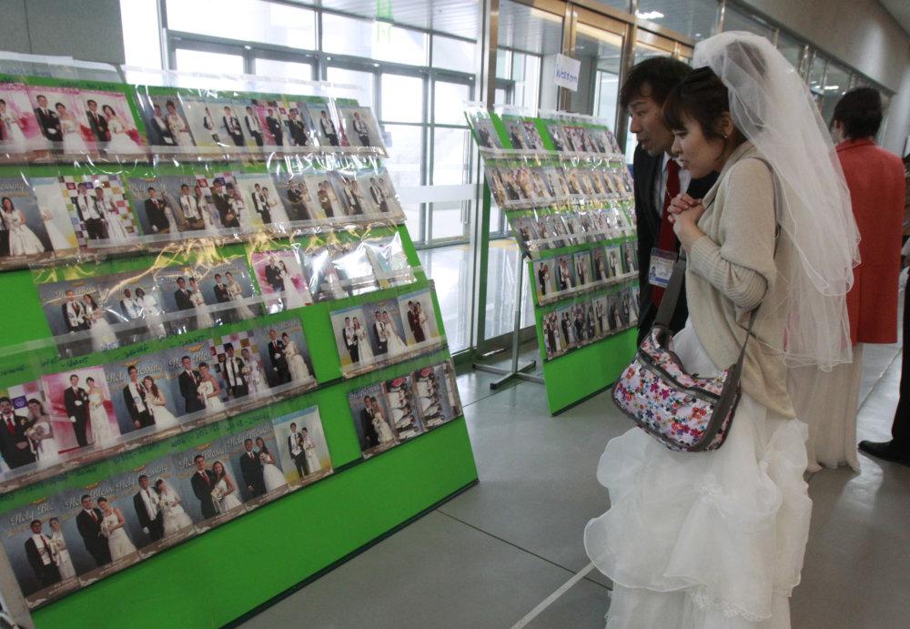 Mladomanželia si hľadajú svoju svadobnú fotku na munistickej svadbe. Niektorých oddával reverend Mun iba cez fotografie. Foto – TASR