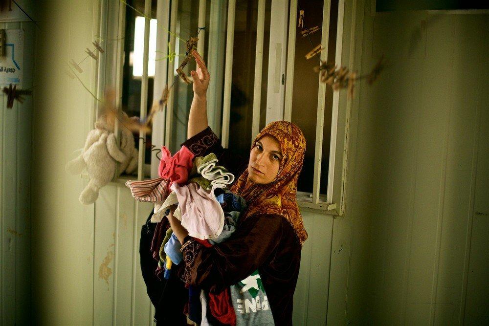 Matka troch detí z Dara'a, zbiera bielizeň vo svojom karavane. Jej manžel hovorí, že v jeho mysli nie je pochýb o tom, že Sýria je jediným miestom, kde môžu žiť. (Foto: Denis Bosnić)