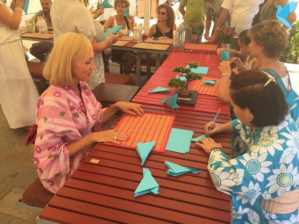 Ambasádorka mieru Renáta Zmajkovičová skladá origami s členkou munistickej cirkvi. Foto – Facebook Ambasádorska mieru