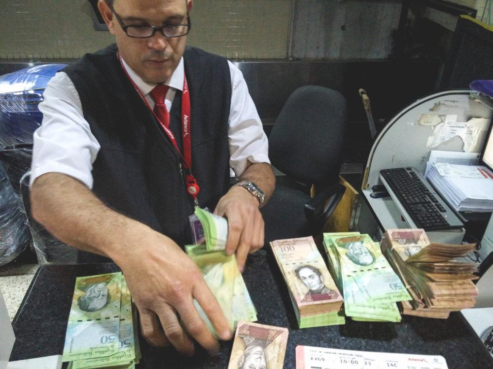 Letištný zriadenec prepočítava stohy bezcenných bankoviek. Dnešná 200-percentná inflácia dosiahne podľa prognóz na konci roka úroveň až 500 percent. Foto - Tomáš Forró
