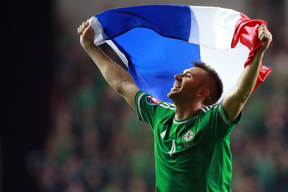 Gareth McCauley oslavuje postup do Francúzska. Severné Írsko sa v ňom stretne v základnej skupine s Poľskom, Nemeckom a Ukrajinou. Northern Ireland's Gareth McCauley celebrates with a French flag with their win over Greece during their Euro 2016 Group F qualifying soccer match at Windsor Park, Belfast, Northern Ireland, Thursday, Oct. 8, 2015. (AP Photo/John McVitty)