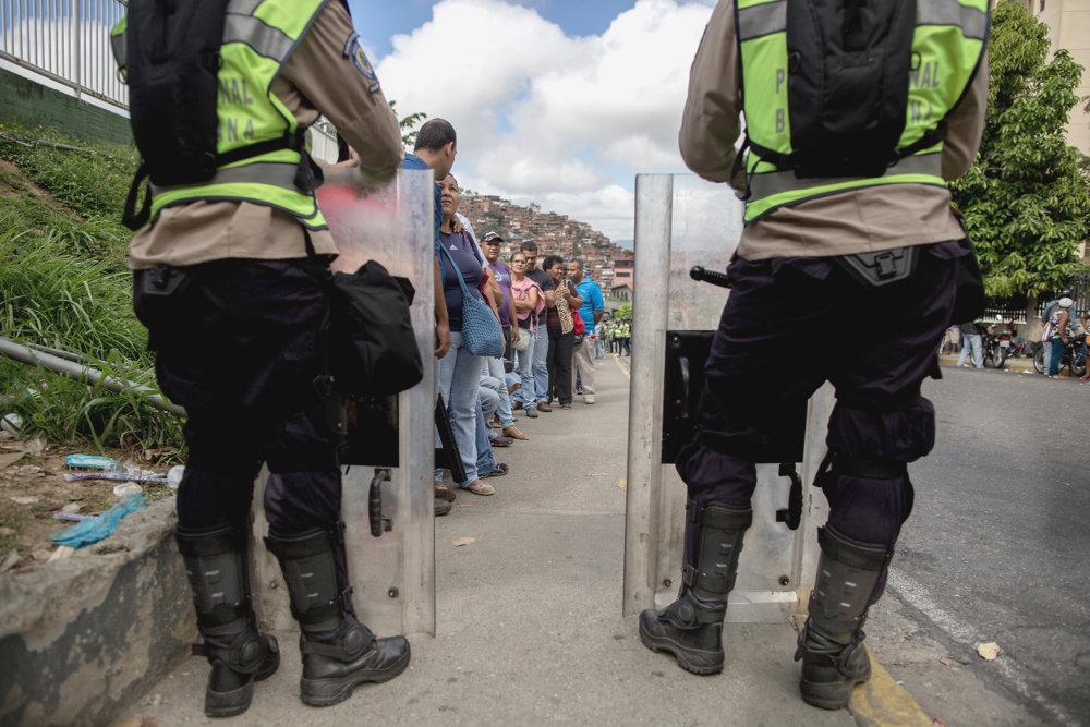 Ľudia stojaci v rade na potraviny, v popredí polícia stráži vládnu štvrť pred prípadnými protestmi. Foto Washington Post – Alejandro Cegarra