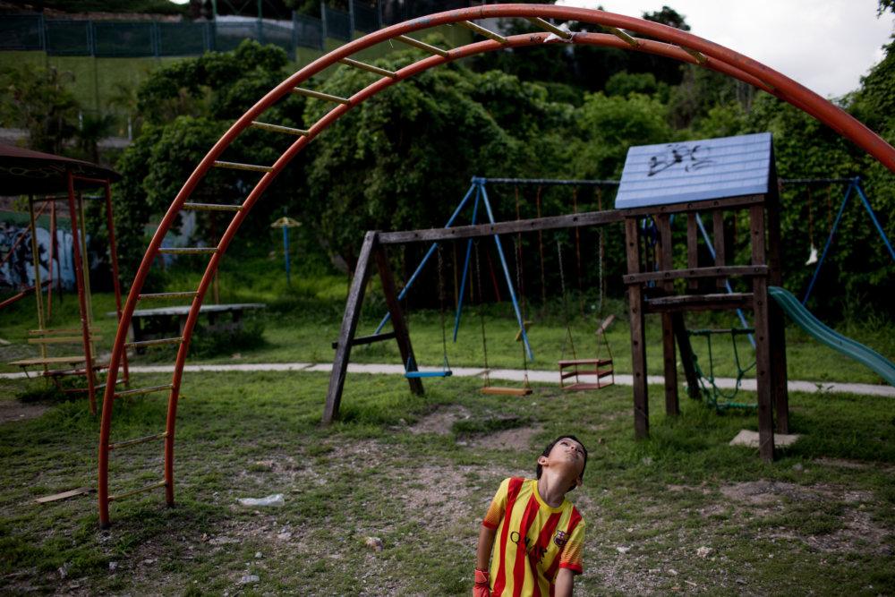 Dieťa sa hrá na zrušenom parkovisku vo štvrti Caracasu, kde žije stredná vrstva. Foto Washington Post - Alejandro Cegarra