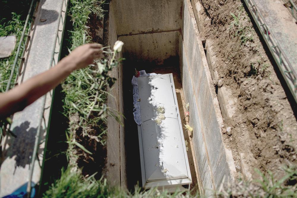 Otec hádže ruže do hrobu svojho syna, ktorého zabil granát počas bojov policajtov s gangmi. Foto Washington Post – Alejandro Cegarra