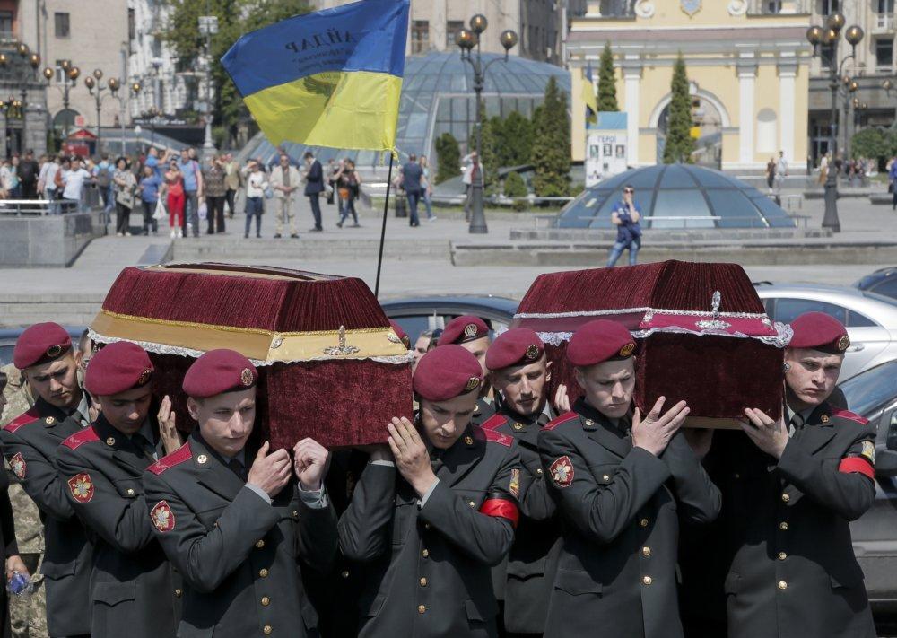 Ukrajinskí vojaci nesú rakvy s pozostatkami svojich zabitých kolegov na Donbase. FOTO - TASR/AP