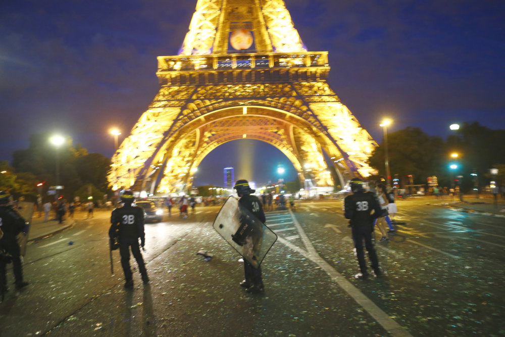 Riot police take positions near the Eiffel Tower in Paris during clashes with young troublemakers during the Euro 2016 final soccer match between Portugal and France at the Stade de France, Sunday, July 10, 2016. (AP Photo/Francois Mori)