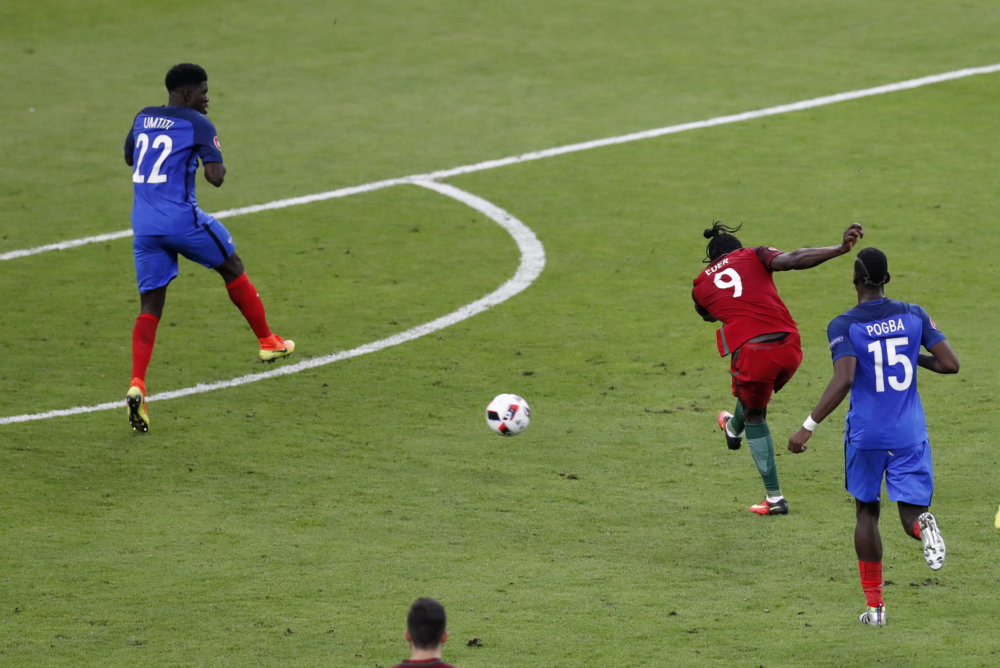 Portugal's Eder, center, scores the opening goal during the Euro 2016 final soccer match between Portugal and France at the Stade de France in Saint-Denis, north of Paris, Sunday, July 10, 2016. (AP Photo/Michael Sohn)