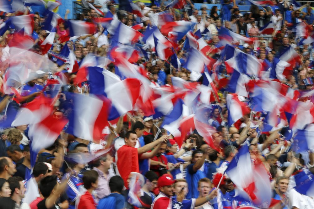 French supporters wave their national flag before the Euro 2016 final soccer match between Portugal and France at the Stade de France in Saint-Denis, north of Paris, Sunday, July 10, 2016. (AP Photo/Michael Probst)