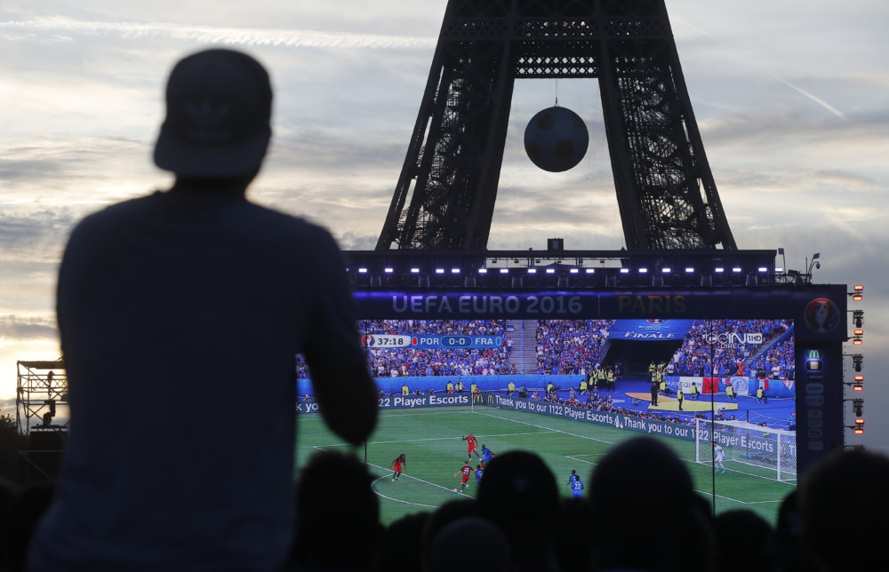 Supporters watch the match in the Paris fan zone in front of the Eiffel Tower during the Euro 2016 final soccer match between Portugal and France, Sunday, July 10, 2016 in Paris. (AP Photo/Laurent Cipriani)