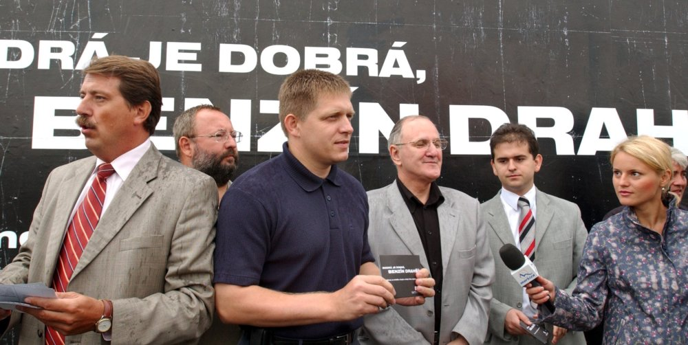 """Robert Fico v roku 2003, za ním bilbord """"Modrá je dobrá, benzín je drahší"""". Foto - TASR"""