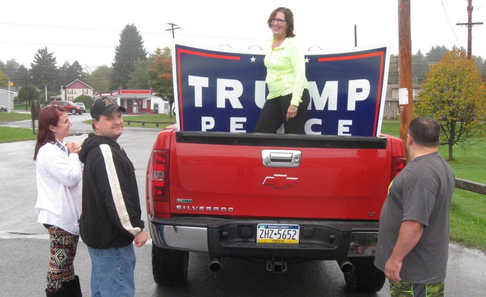 Jackie Kulbacková (v žltom) pomáha sympatizantom Trumpa dať veľký pútač na korbu auta. Foto - autor