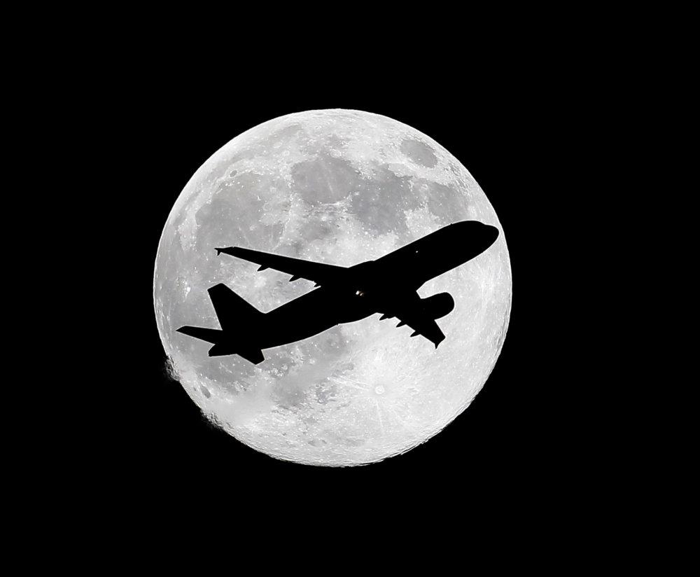 """KK8 Whittier - Na snímke silueta lietadla pred takmer úplným supermesiacom 11. júla 2014 v americkom Whittieri. Cez víkend na oblohe uvidíte superspln alebo supermesiac. Ide o moment, kedy je mesiac v splne a zároveò ve¾mi blízko Zeme. FOTO TASR/AP One day before a """"supermoon,"""" a commercial airliner crosses the waxing gibbous moon on its final approach to Los Angeles Airport as viewed from Whittier, Calif., Friday, July 11, 2014. (AP Photo/Nick Ut)"""