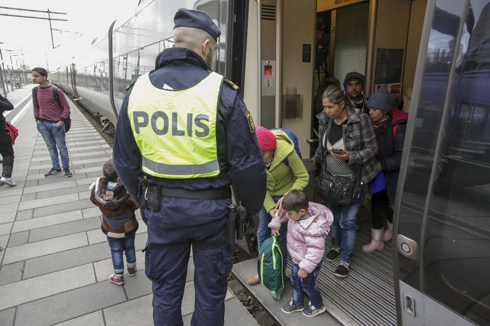 Švédsky policajt kontroluje skupinu migrantov vystupujúcich z vlaku z Dánska vo švédskom Malmö. Foto - TASR/AP