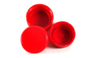 Red plastic bottle screw caps isolated on white