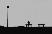 The silhouette of woman sitting alone with grey sky, concept of