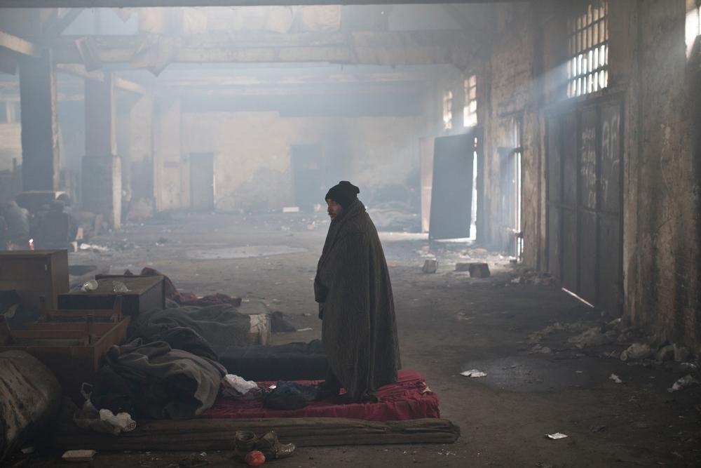 Muž stojí v starom železničnom sklade, kde teraz žijú migranti. Foto - Marko Drobnjakovic/Lekári bez hraníc