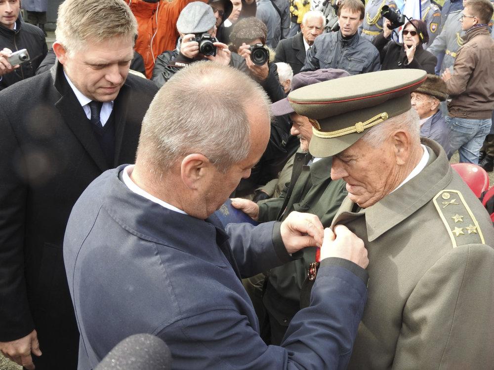 Na po¾sko-slovenskom pohranièí na Dukle vzdali 6. októbra 2016 pri príležitosti 72. výroèia Karpatsko-duklianskej operácie a Dòa hrdinov Karpatsko-duklianskej operácie predstavitelia SR úctu obetiam a bojovníkom, ktorí položili životy v neïalekých lesoch poèas jednej z najažších bitiek druhej svetovej vojny. Na snímke druhý sprava minister obrany SR Peter Gajdoš s oceneným úèastníkom pietneho aktu, v¾avo sa pozerá premiér SR Robert Fico . FOTO TASR - Michaela Zdražilová *** Local Caption *** Karpatsko-duklianska operácia Vyšný Komárnik Dukliansky priesmyk druhá II. svetová vojna vojnový konflikt cintorín obete padlí bojovníci vojaci pylón Karpatsko-dukelský Pamätník Èeskoslovenského armádneho zboru Deò hrdinov Karpatsko-duklianskej operácie - pamätný deò SR