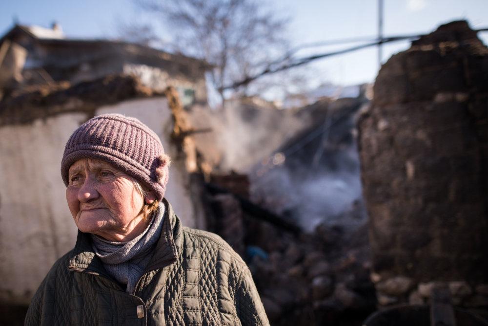 Babka a jej zničený dom po ostreľovaní v starej časti Avdijivky. Foto N - Vladimír Šimíček