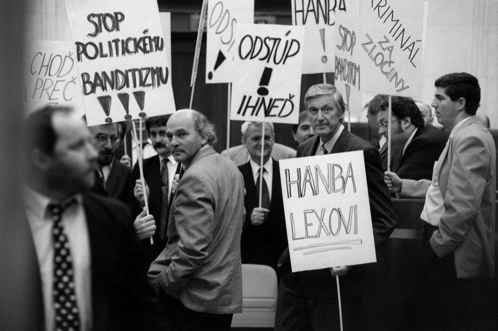 """Protest parlamentnej opozície proti Ivanovi Lexovi v roku 1996. """"Stop politickému banditizmu, Odstúp, Choď preč z parlamentu, SIS – ŠtB, Hanba Lexovi, Stop politike zločincov"""". Foto – TASR"""