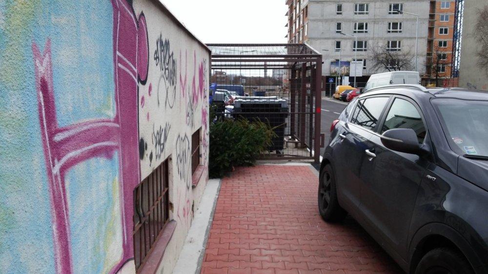 Chodník so zaparkovým autom pričom nalavo za rohom je skrytý kontajner na nepotrebný textil.