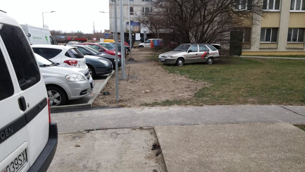 Dva vraky mimo parkoviska. Vpredu felícia s otvoreným kufrom a vzadu firemné úžitkové vozidlo na trávniku. Tretí vrak je zaparkovaný na úrovni druhého stĺpu verejného osvetlenia.