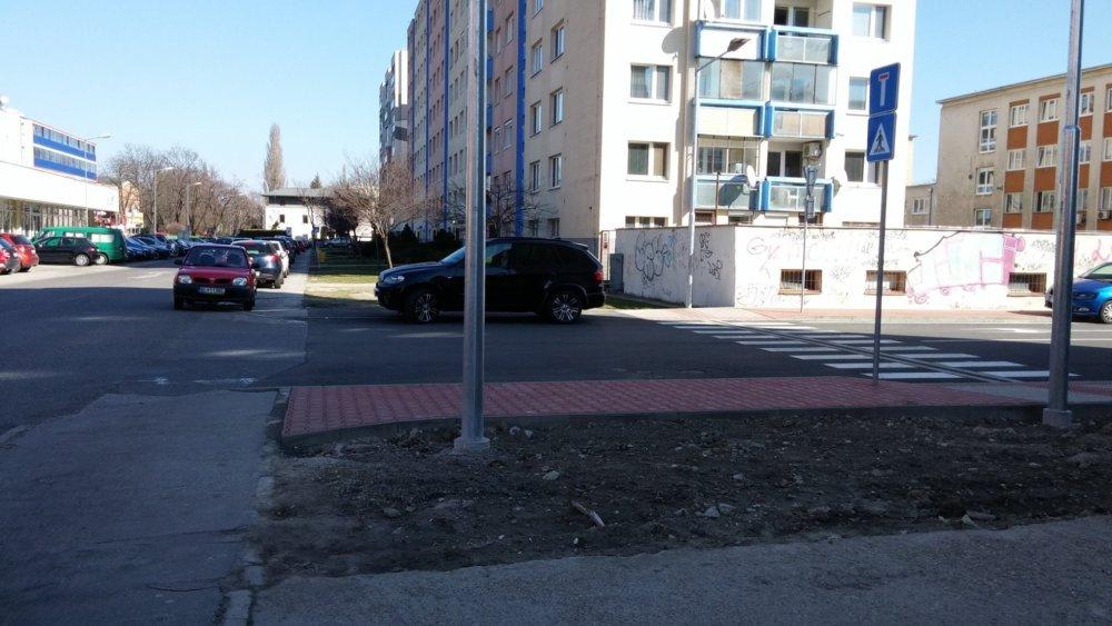 Vlavo zvyšky pôvodného priechodu na Nobelovej a vpravo nový priechod. Nový chodník už slúži ako parkovisko.