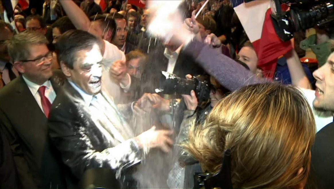 A video grad made on April 6, 2017 shows French presidential election candidate for the right-wing Les Republicains (LR) party Francois Fillon (C) reacting as a man throw flour at him on April 6, 2017 during a political rally in Strasbourg, northeastern France. / AFP PHOTO / Julien SENGEL / RESTRICTED TO EDITORIAL USE
