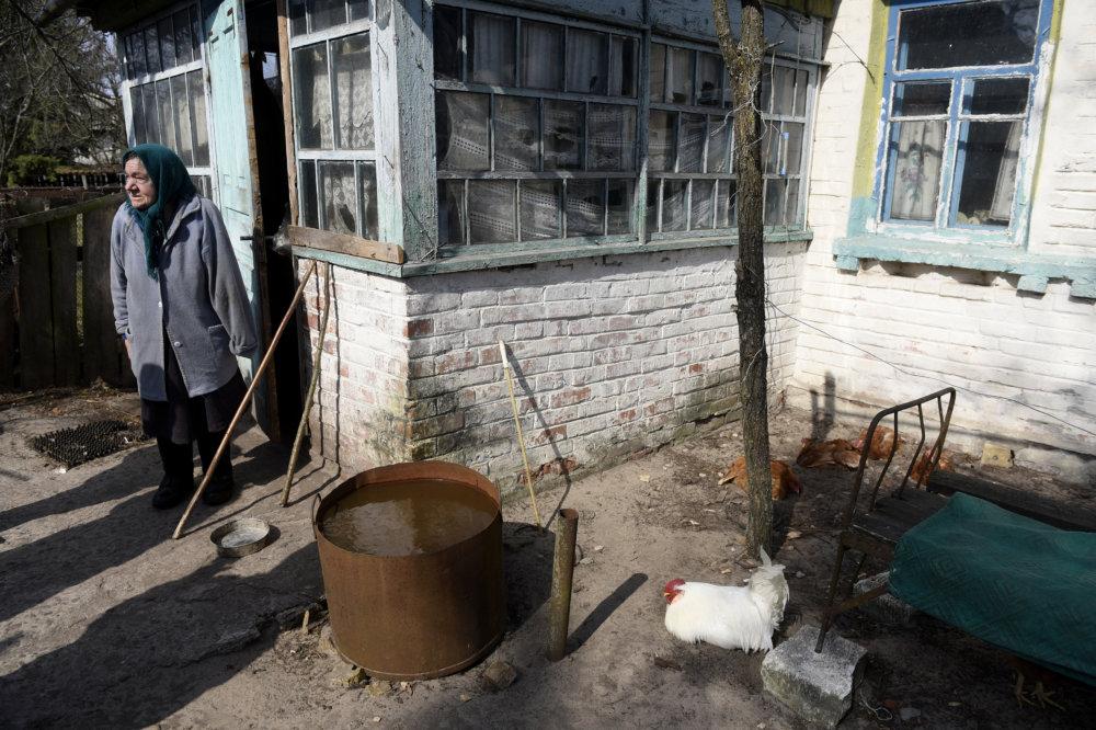 Jedna z pôvodných obyvateliek, ktorá sa vrátila žiť do rodného domu v uzavretej zóne neďaleko mesta Černobyľ. Foto - TASR