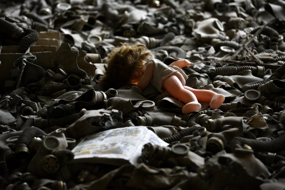 Plynové masky a bábika na podlahe základnej školy v ukrajinskej Pripiaťi pri elektrárni. Mesto bolo vybudované pre rodiny zamestnancov, žilo tam približne 50-tisíc obyvateľov. Po výbuchu bolo celé evakuované, už sa tam nikto nevrátil žiť a preto ho prezývajú mestom duchov. Foto - TASR
