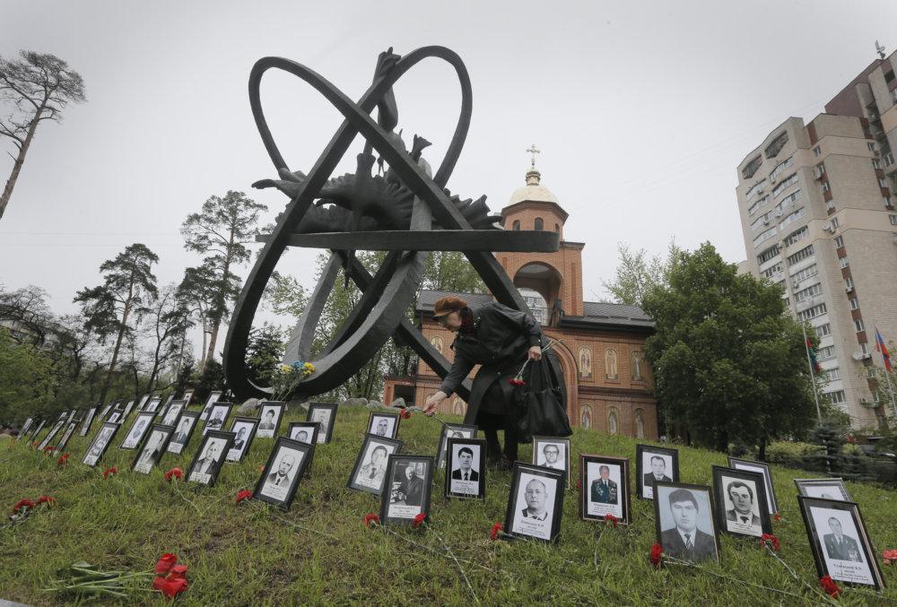 Príbuzná obete pokladá kvety medzi fotky vedľa pamätníka za obete havárie v jadrovej elektrárni v Černobyle, 26. apríla 2016 v Kyjeve. FOTO - TASR/AP