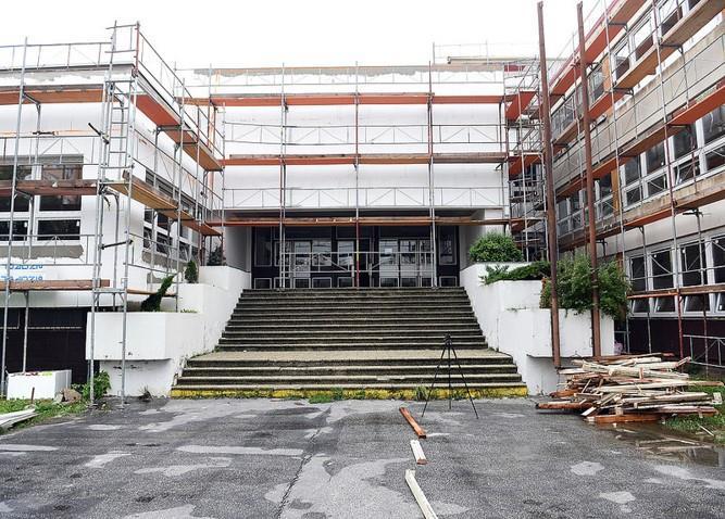 Budova školy obložená lešením pri jej zateplovaní