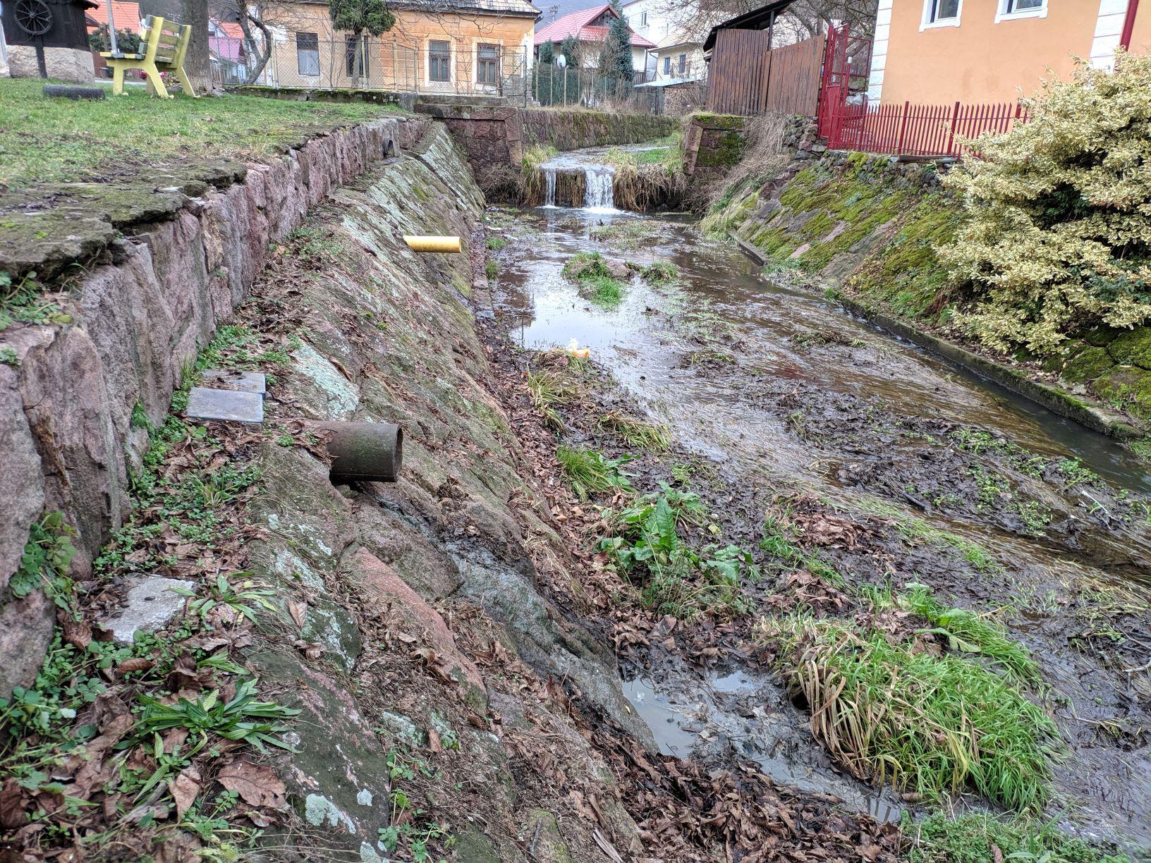 Realita mnohých obcí na Slovensku - potok s tvrdými brehovými opevneniami, bariérou, vyústením kanalizácie a úplne bez brehovej vegetácie. © Miro Očadlík, WWF Slovensko.